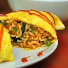 """Một món nữa khá hay là mì trứng Soba. Mì đã được chế biến vừa miệng với hành, rau cải, nước sốt, sau đó khéo léo cuộn một lớp trứng vàng ươm bên ngoài, rồi """"tô vẽ"""" thêm bằng tương ớt đỏ tươi. Mì trứng Soba đẹp mắt, thú vị cũng đủ độ đạm giá 45.000 đồng."""